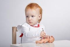 扮演有玩偶的女孩医生 免版税库存照片