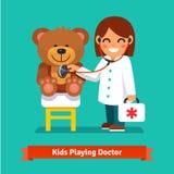 扮演有玩具熊玩具的小女孩一位医生 免版税库存图片