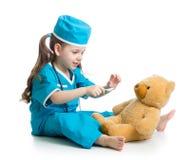 扮演有玩具熊的孩子女孩医生 免版税库存图片