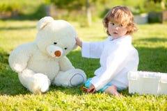 扮演有玩具熊的小女孩学龄前儿童医生户外 库存照片