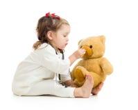扮演有长毛绒玩具的儿童女孩医生 免版税库存图片