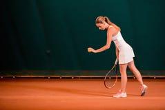扮演运动员的室内网球场 免版税库存照片