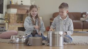 扮演音乐家的兄弟和姐妹孪生打罐和盘与大匙子和笑获得乐趣 股票录像