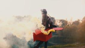 扮演飞行员的愉快的女孩,跑在乐趣平面服装的惊人的日落湖附近有颜色烟慢动作的 股票录像