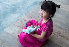 扮演医生或护士有长毛绒玩具熊的可爱的亚裔女孩 免版税库存照片