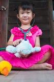 扮演医生或护士有长毛绒玩具熊的可爱的亚裔女孩 图库摄影