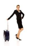 扯拽被转动的手提箱的微笑女实业家 库存图片