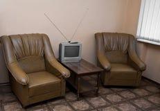 扶手椅子、一张桌和电视在屋子里 免版税库存照片