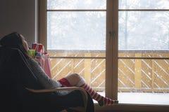 扶手椅子的妇女在一个多雪的窗口前面 免版税库存图片