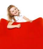 扶手椅子的快乐的小女孩 库存图片