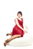 扶手椅子礼服红色坐的妇女 免版税库存照片