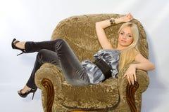 扶手椅子金发碧眼的女人 免版税图库摄影