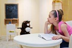 扶植下巴观察书的小女孩梦想 免版税库存照片
