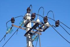 扶植在蓝色无云的天空的电源线上面  免版税库存照片