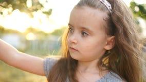 扶植她的面孔的相当讨人喜欢的小女孩画象在夏天绿色公园 女孩挥动她的筷子 股票录像