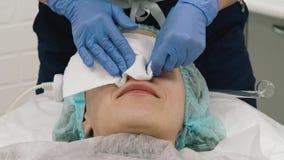 扶植客户的面孔的美容师的特写镜头用一张纸巾 股票录像
