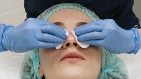 扶植客户的面孔的美容师的特写镜头用一张纸巾 股票视频