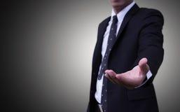 扶养穿着蓝色衣服的商人发光在灰色背景或在企业概念后 免版税库存照片