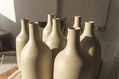 批的正面图射击从灰色颜色未加工的陶瓷材料的传统手工制造瓶设计在烹调以后在日落时间 免版税库存图片