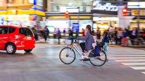 批评不明身份的妇女的摄影有儿童骑马自行车的夜在涩谷广场 的treadled 库存照片