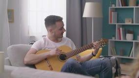 批评人在一个舒适客厅弹他的朋友的吉他 股票录像