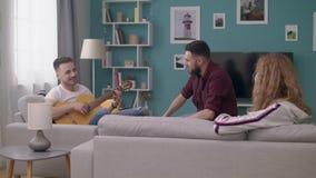 批评年轻人在一个舒适客厅弹他的朋友的吉他 影视素材