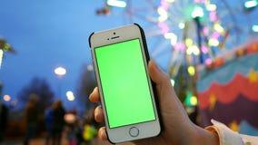 批评拿着有一个绿色屏幕的女性手射击巧妙的电话 股票录像