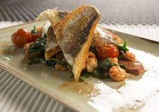 批评油煎的鲈鱼用小龙虾、加调料的口利左香肠、婴孩菠菜&西红柿 免版税库存照片