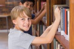 寻找书的逗人喜爱的学生在图书馆里 库存图片