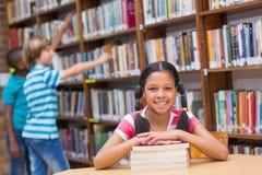 寻找书的逗人喜爱的学生在图书馆里 图库摄影