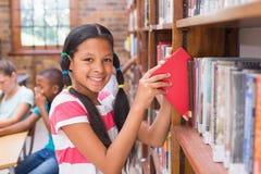 寻找书的逗人喜爱的学生在图书馆里 免版税库存照片