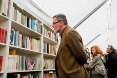 寻找使用的书的夹克的年长人 图库摄影