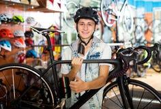 寻找和尝试新的赛跑的自行车的男孩 免版税库存照片