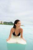 寻找在冲浪板的冲浪的冲浪者女孩海浪 库存图片