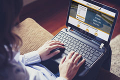 寻找在家在有膝上型计算机的一个房地产网站的妇女,当坐沙发时 库存照片