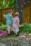 寻找复活节彩蛋的两个男孩 免版税库存照片