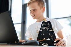 寻找改善的被启发的男孩为他的机器人打翻 免版税库存图片