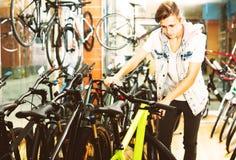 寻找新的体育自行车的微笑的男孩 免版税库存照片