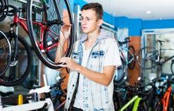 寻找新的体育自行车的笑的十几岁的男孩 库存照片