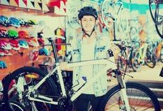 寻找新的体育自行车的年轻十几岁的男孩 免版税库存图片
