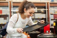 寻找新的平底锅和罐的女孩 免版税库存照片