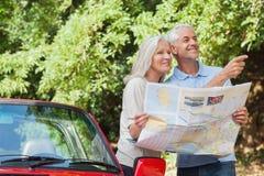 寻找方向的快乐的成熟夫妇读书地图 免版税库存照片