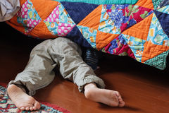 寻找某事的孩子在床下 库存照片
