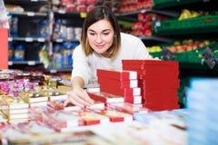 寻找鲜美甜点的可爱的女孩顾客在超级市场 库存图片