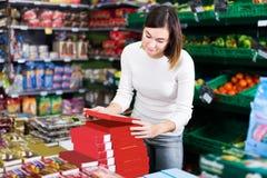 寻找鲜美甜点的女孩顾客在超级市场 免版税库存照片