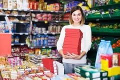 寻找鲜美甜点的微笑的女孩顾客在超级市场 免版税库存照片