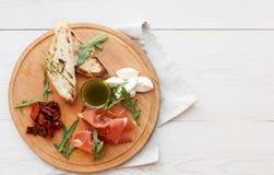 承办酒席与熏火腿和无盐干酪的盛肉盘开胃小菜 免版税图库摄影