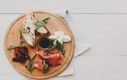 承办酒席与熏火腿和无盐干酪的盛肉盘开胃小菜 免版税库存图片