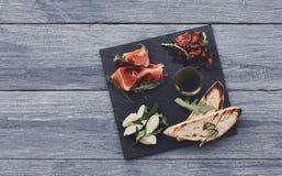 承办酒席与熏火腿和无盐干酪的盛肉盘开胃小菜 免版税库存照片