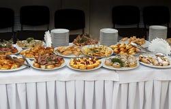 承办酒席与被烘烤的食物快餐、三明治、蛋糕、杯子和板材的宴会桌 库存图片